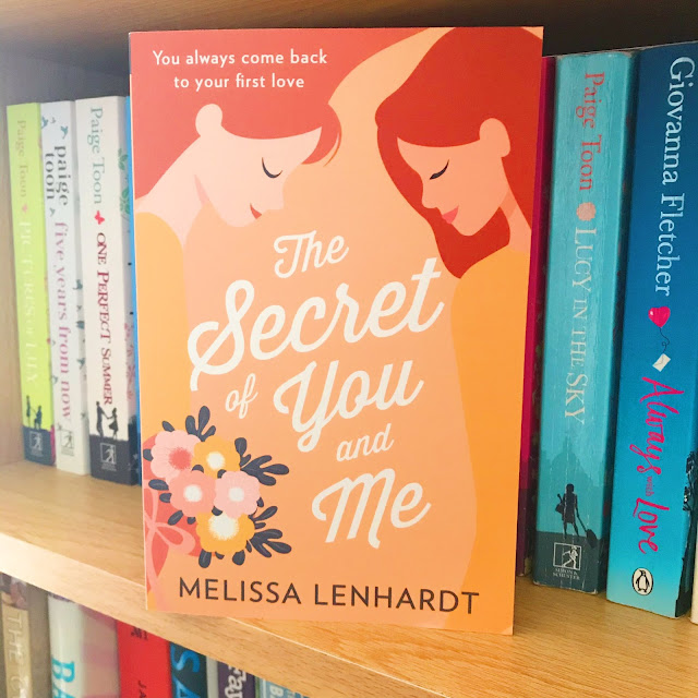The Secret of You and Me by Melissa Lenhardt book placed on bookshelf in front of row of other books