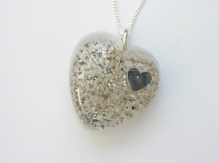 Resin heart shaped pendant containing ashes, silver glitter and a silver heart