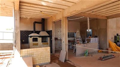 A varanda gourmet e a cozinha do sobrado em fase de acabamento, salientando a integração entre os ambientes compostos por forno de pizza, churrasqueira e cooktop (fogão de ilha) com o devido equipamento de exaustão.