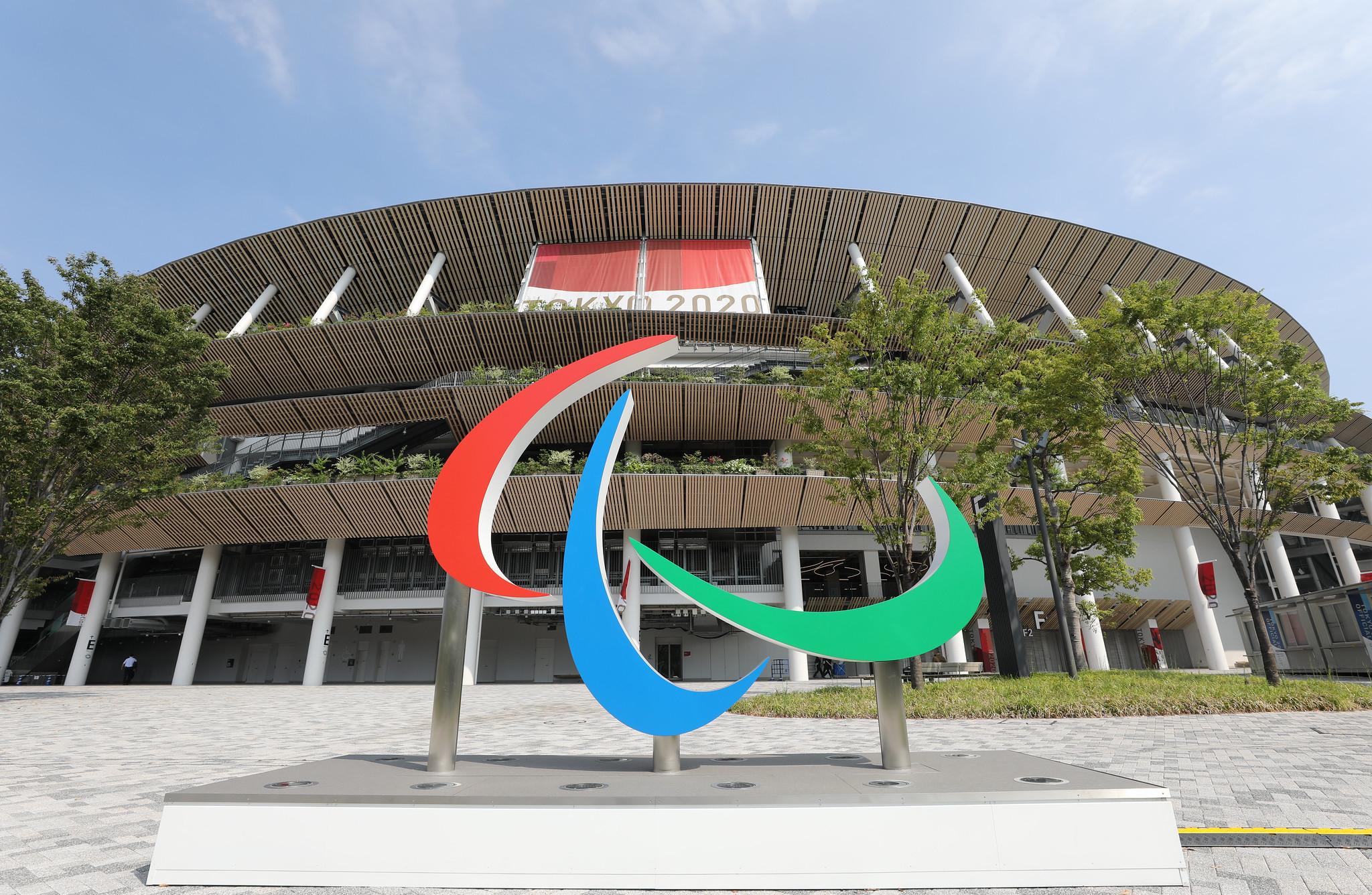 Foto em grande angular, com escultura dos Agitos em primeiro plano, com Estádio Olímpico ao fundo