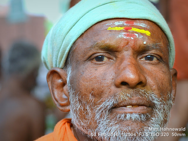 Matt Hahnewald Photography; Facing the World; closeup; street portrait; headshot; outdoor; Asia; South Asia; India; Tamil Nadu; Tiruchirappalli; Srirangam; Ammamandapam; ghats; Nikon D3100; Nikkor AF-S 50mm f/1.8G; travel; travel destination; beggar; photography; colour; portraiture; person; people; eyes; eye contact; Indian man; face; short grey beard; poor; horizontal; ethnic; modern India; Shaivite devotee; tilaka mark