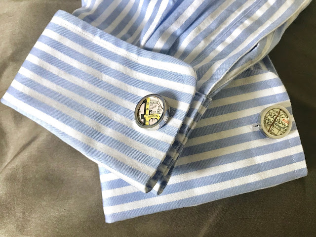 Personalised map cufflinks in a blue and white striped shirt, laid out on a silver fabric background