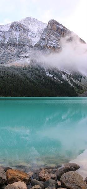 خلفية بحيرة صافية مياهها فيروزية اللون ورائها جبل