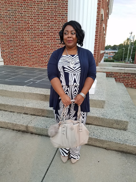 Plus size blogger with jumpsuit, heels, and nude handbag