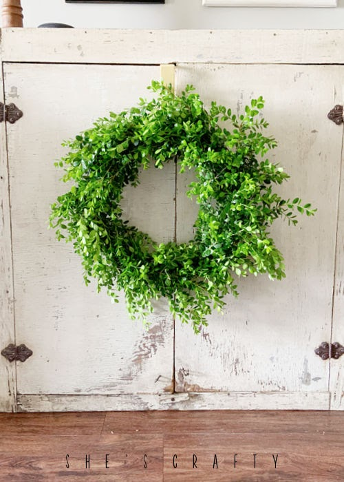 Hanging boxwood wreath in antique cabinet doors.
