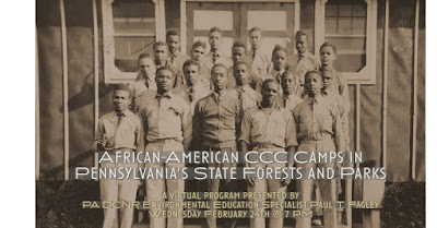 Black men in CCC uniforms stand in four rows with a CCC camp building behind them