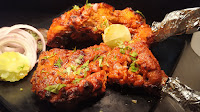 Cooked two pieces of Tandoori chicken with onions and lemon for Tandoori chicken recipe