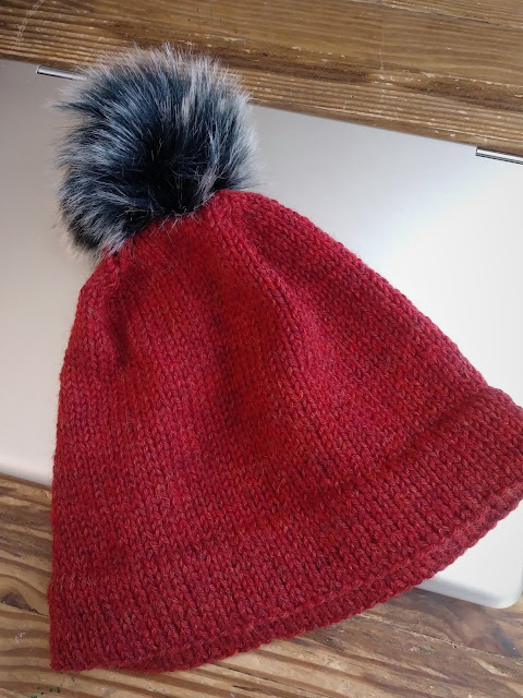 Red knit hat with black and silver faux fur pompom