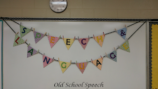Chevron banner hanging on white board that spells out Speech & Language