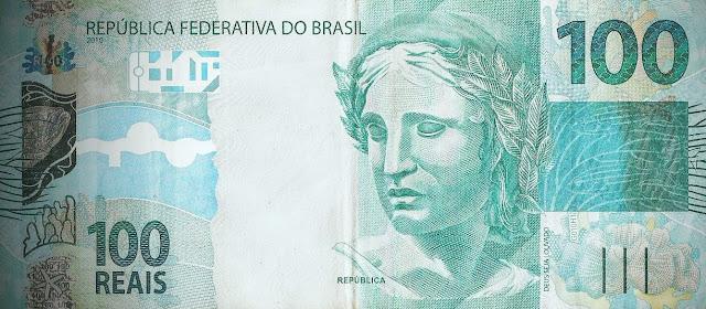 A foto mostra uma cédula de Cem Reais do dinheiro do Brasil.