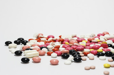 A picture of different colored drug tablets.