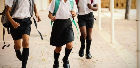 Mid shot of children in school uniform walking to class
