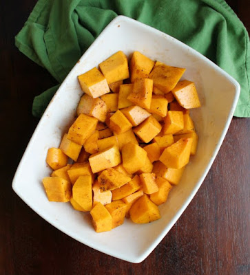 cubes of butternut squash tossed in oil and seasoning and ready to go into the air fryer