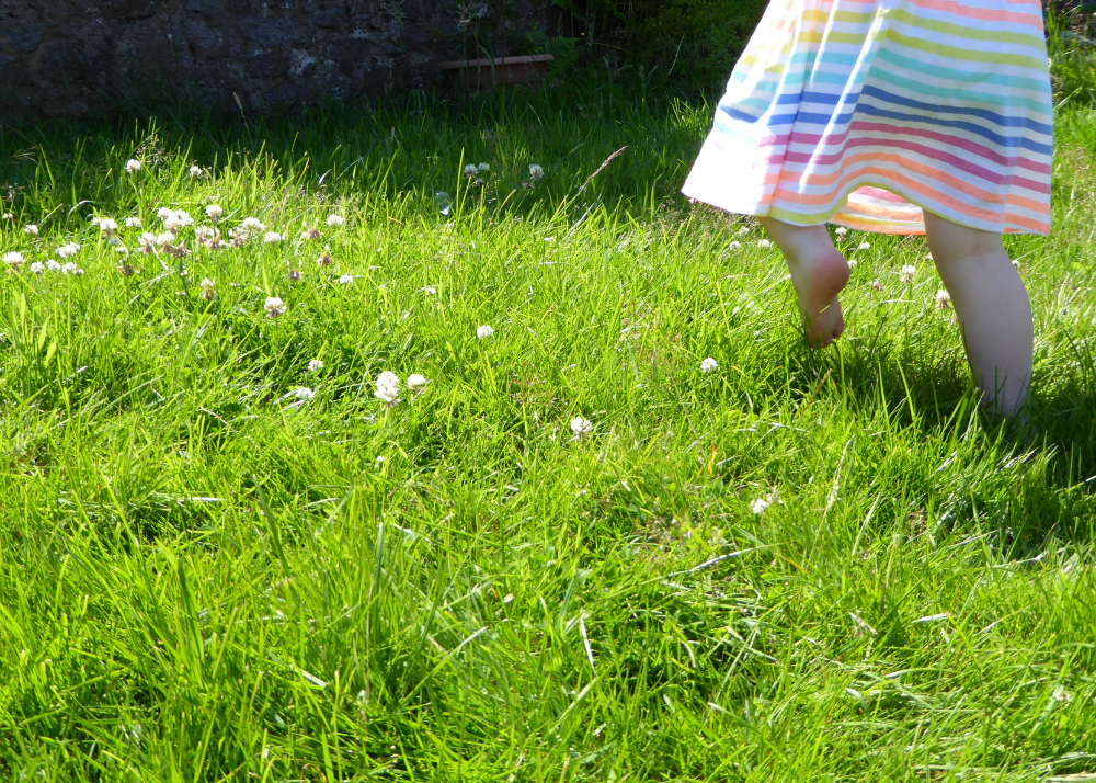Toddler feet running in grass
