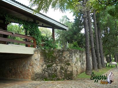 Muro de pedra na parte inferior e nas paredes da garagem da casa com os guarda corpos de madeira no terraço da casa em sítio em Bragança Paulista-SP com o calçamento de pedra paralelepípedo.
