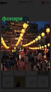 В вечернем городе развешаны гирлянды из светящихся фонарей