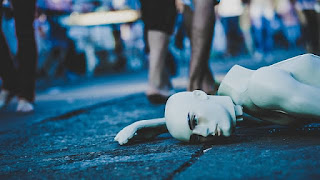 manequim deitado na calçada movimentada