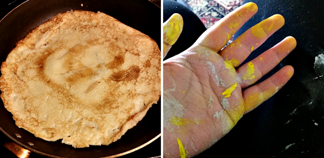 A pancake in a pan and my hand covered in grey and yellow paint.