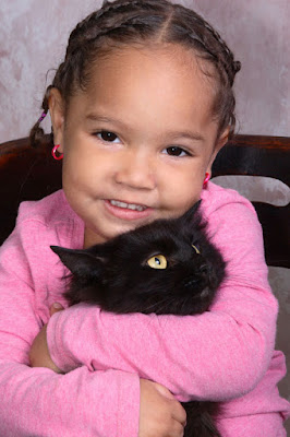 A young girl hugs her pet cat, but what do young children learn from their pets? It helps with understanding biology, research shows.