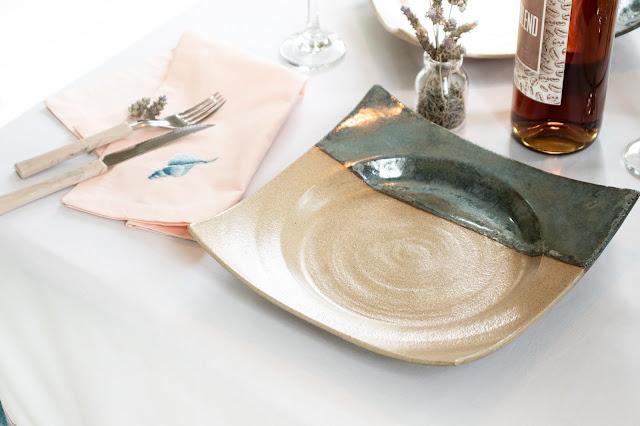 Prato de cerâmica com guardanapo rosa ao lado