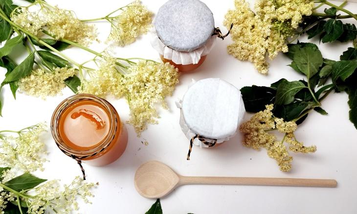 Holunderblütengelee mit Holunderblüten und Gläsern und Kochlöffel