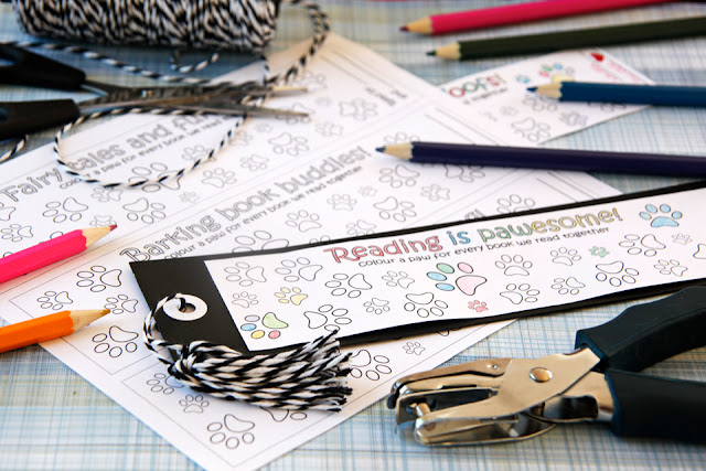 Bookmarks with colouring-in paw prints on a table with craft supplies and coloured pencils