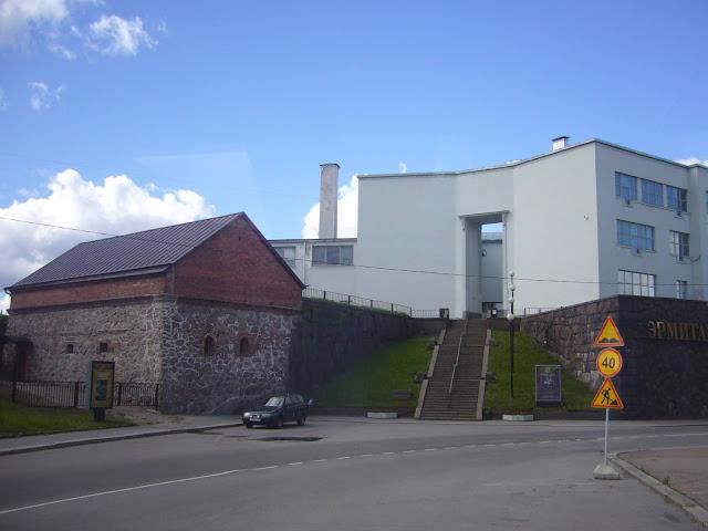 Katu, vanha harjakattoinen kivirakennus ja valkoinen taidekoulu ja -museorakennus. Värivalokuva.
