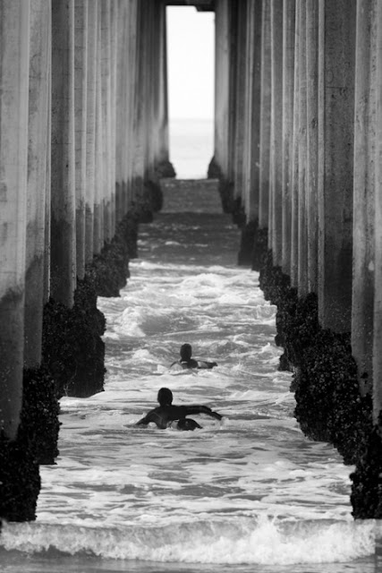 Two boys swimming beneath pier