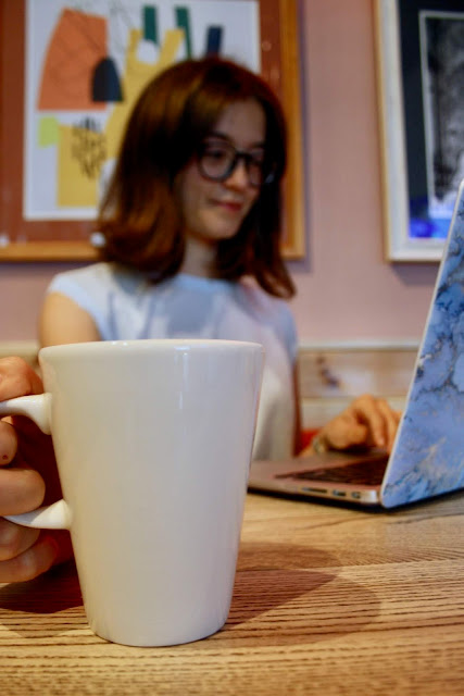 Close up of Abbey's coffee cup. She works at a laptop in the background