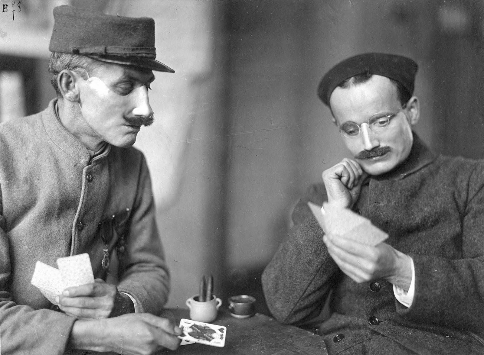 Two soldiers play cards while wearing Ladd's handiwork.