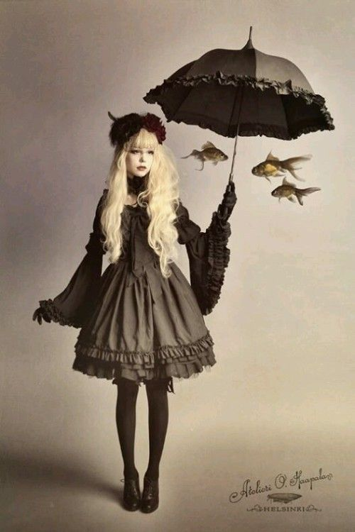 Girl with a gothic lolita style holding an umbrella with fishes underneath