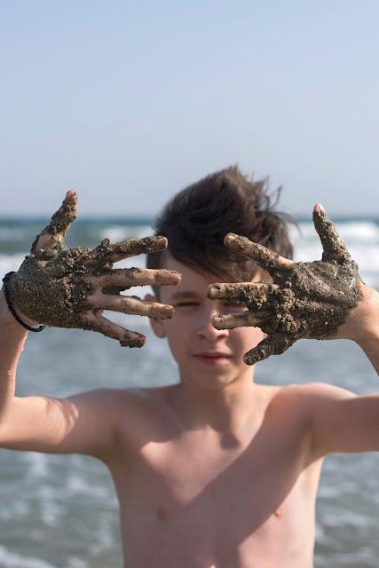 Милый мальчик с грязными руками на пляже