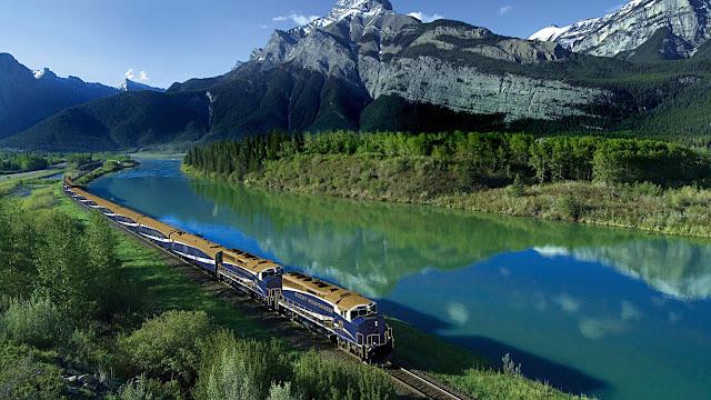 tren a orillas del río a través de las montañas rocosas