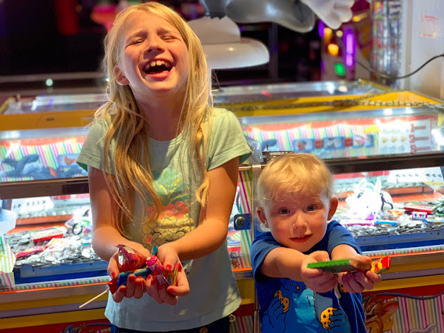 Children showing off the sweets they have won in the arcade with 10p slots in the background