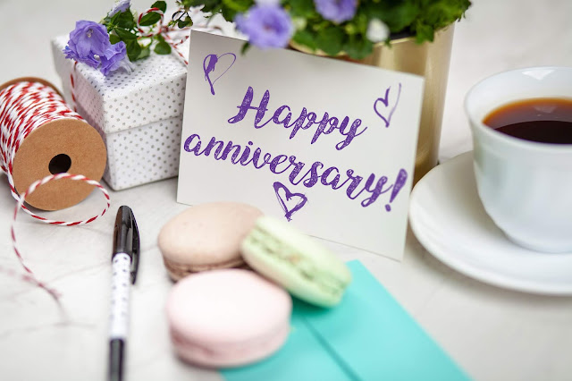 "A table card with a ""Happy Anniversary!"" text, and surrounded by coffee, twine, gift box, and macarons."