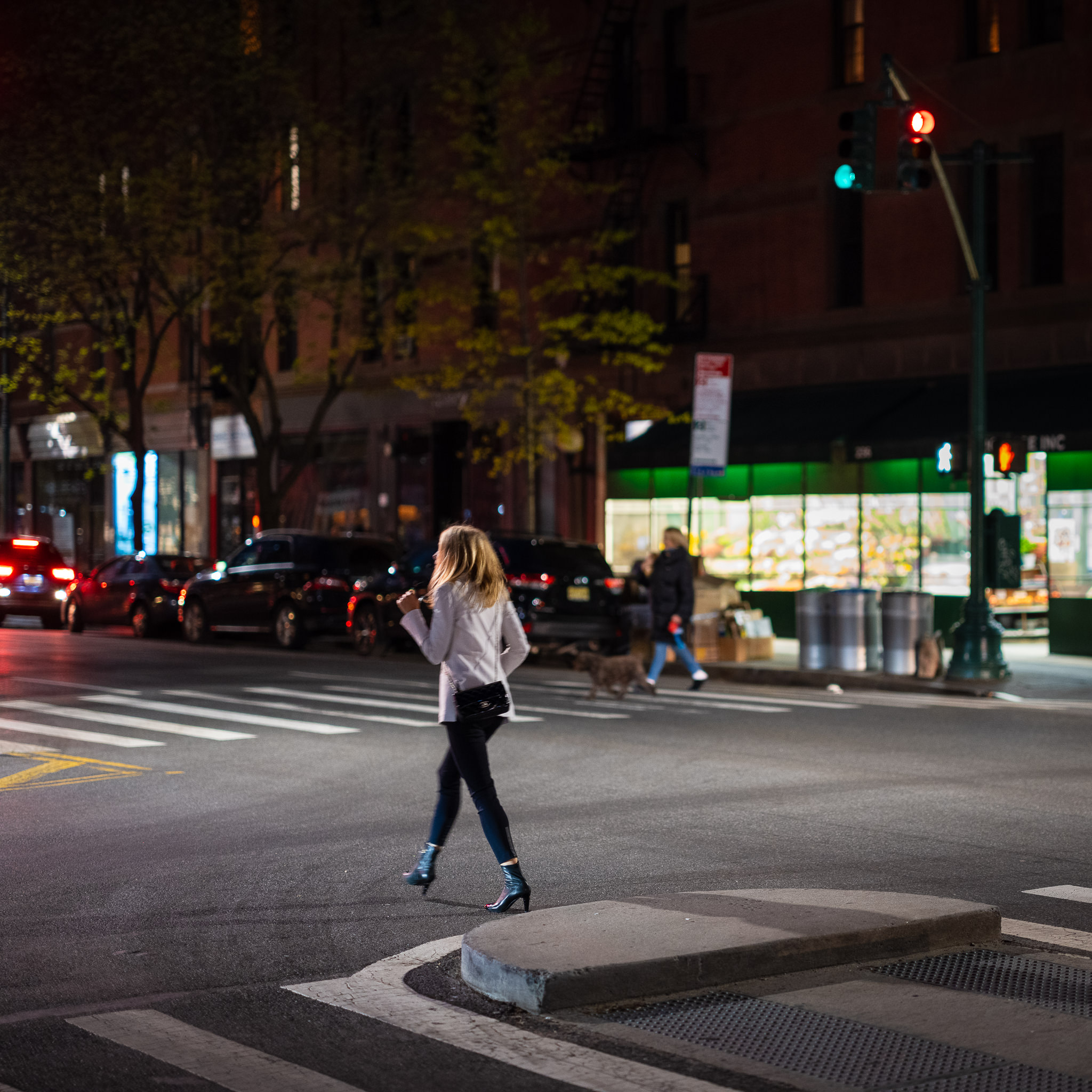 a photo of a well dressed lady crossing the street in new york