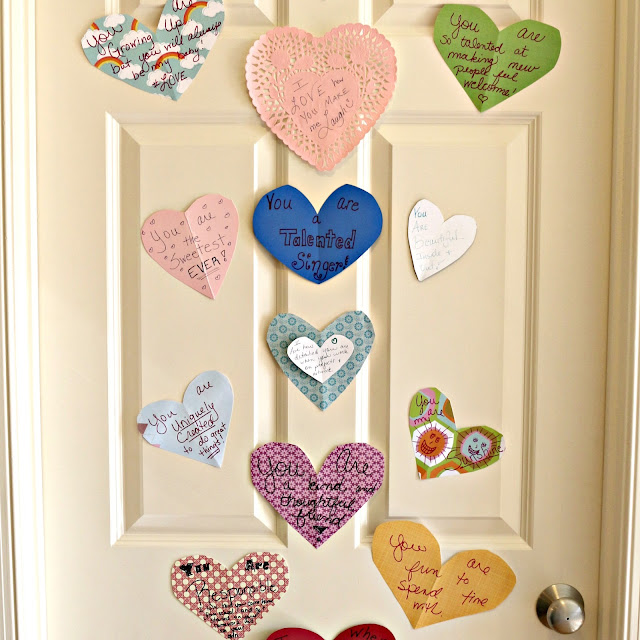 Cutout hearts with notes of encouragement are taped to the door