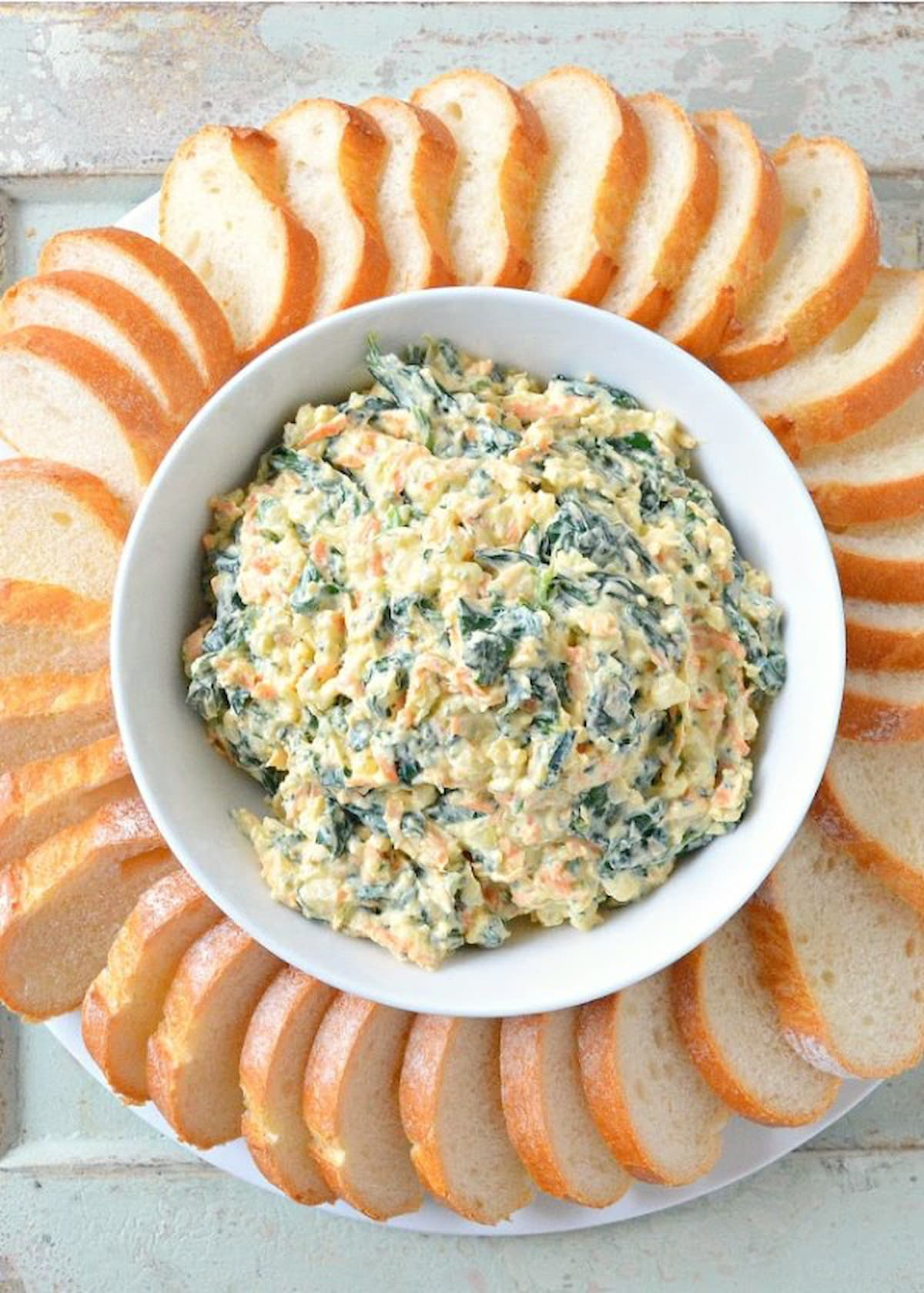 Homemade Spinach Dip Recipe from scratch in a white bowl with bageutte around the edge.