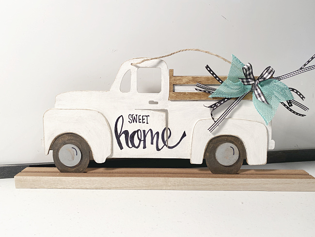 white distressed truck with a teal bow
