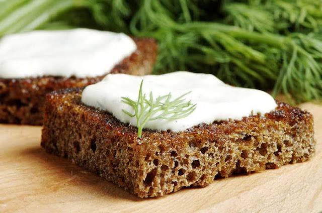 Primer planode una tostada de pan casero con salsa griega con yogur y ajo