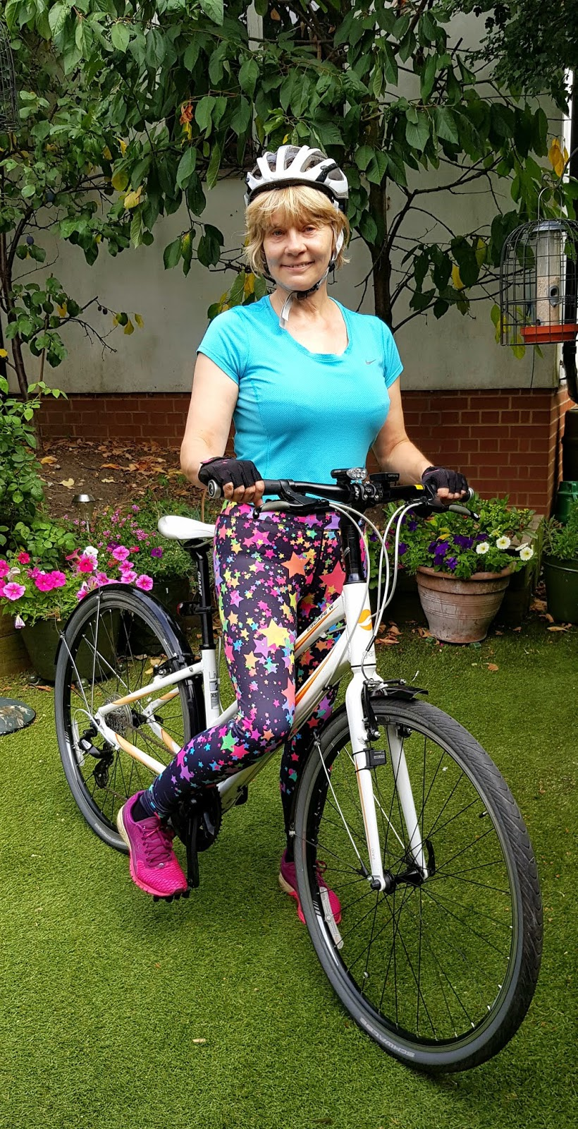 Middle aged woman in cycling helmet and colourful leggings on bike
