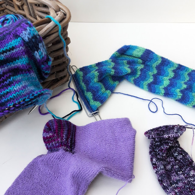A basket containing a half-knitted blue and purple sock.  To the right is a blue Neat Ripple sock, to the left in front is a purple sock and to the right at the front is a purple mottled sock.  All are half-knitted