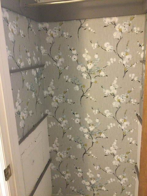 closet in bathroom being wallpapered