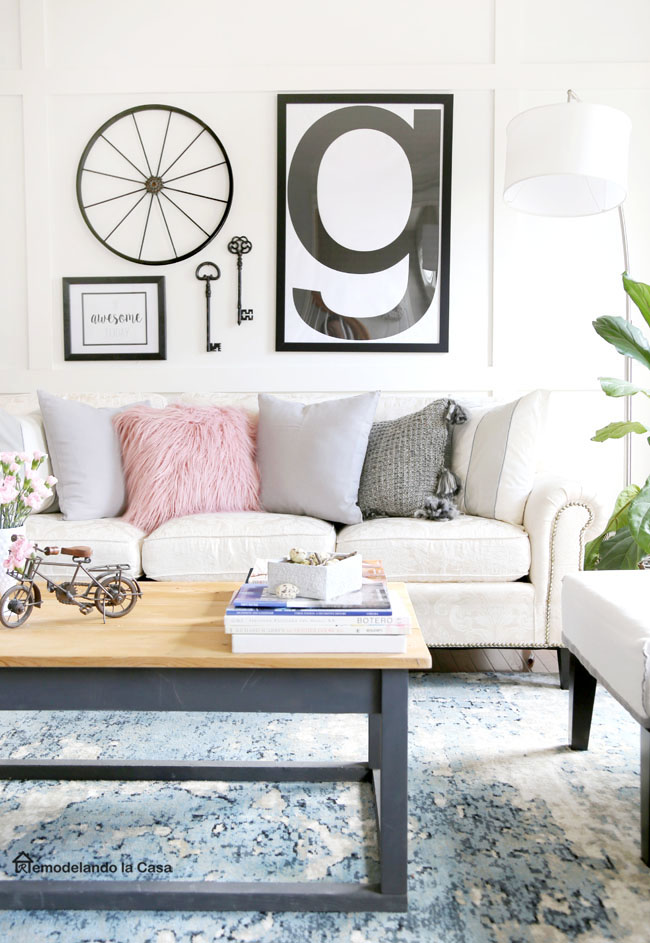 A living room with a black and white gallery wall with letter G wall art, pink accents on the coffee table and pink and grey pillows on the sofa.
