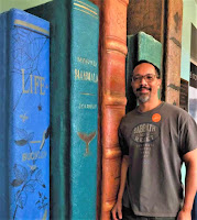 """Photo of Stephen De La Vega standing next to the spines of books that are larger than life. Most prominent book is title """"Life."""""""