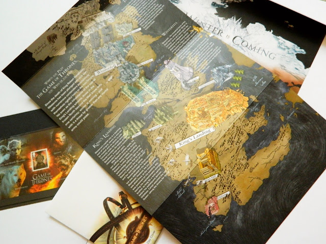 A photo showing a Westeros map from Game of Thrones and some stamps