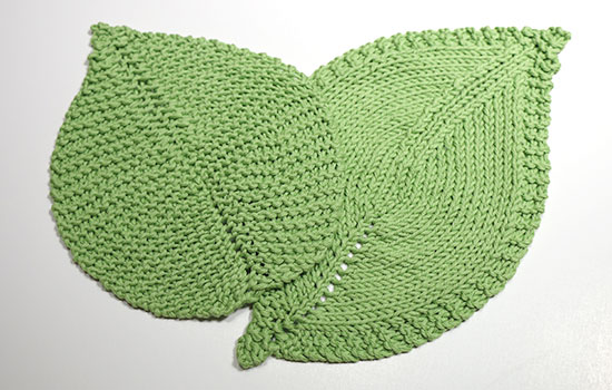 Two green washcloths or dishcloths hand knit in the shapes of leaves on a white background.