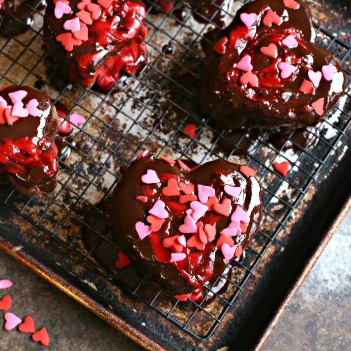 Recipe for heart shapes cut out of a chocolate sheet cake and topped with ganache and sprinkles.