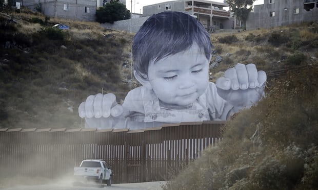 Giant portrait of toddler appears over US-Mexico border wall