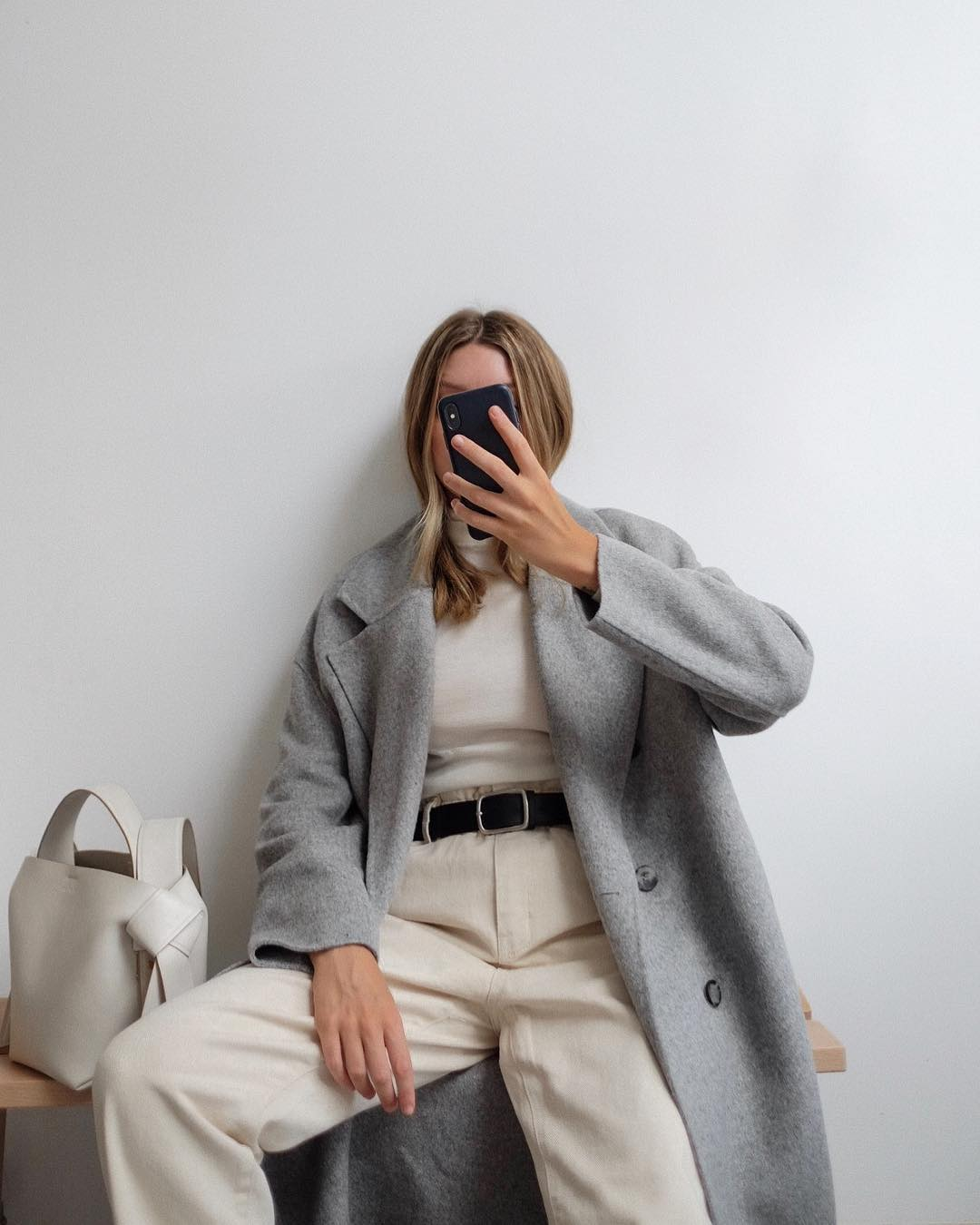 22 Grey Coats We Can't Get Enough Of — Brittany Bathgate in a grey coat, beige turtleneck, high-waisted pants and Acne Studios bag